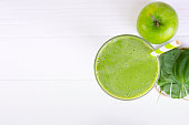 Spinach mix apple smoothie green juice beverage healthy the taste yummy in glass for on white wood background from the top view.