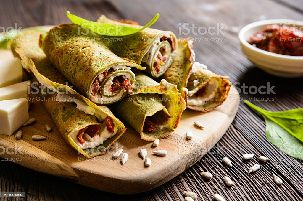 Spinach pancakes stuffed with Feta, curd and sun dried tomato stock photo
