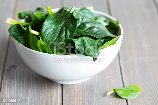 Fresh spring baby leaves of spinach on wood table.