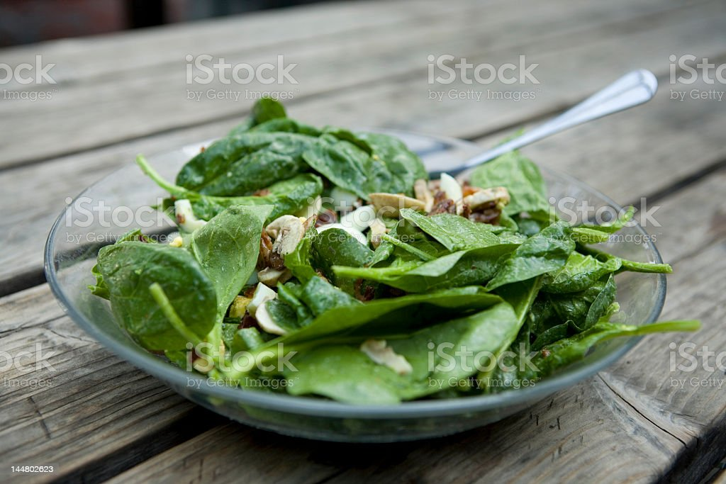 Spinach salad with almonds on dark wood royalty-free stock photo