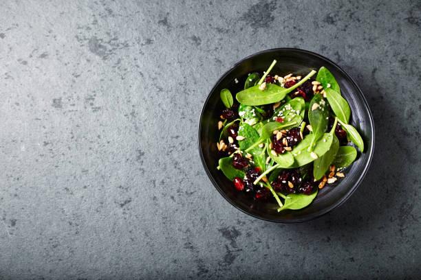 salade d'épinards avec des canneberges séchées et graines de grenade - saladier photos et images de collection