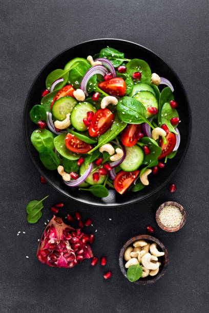 Spinach salad with fresh cucumbers, tomato, onion, pomegranate, sesame seeds and cashew nuts on black background. Healthy vegan food. Top view stock photo