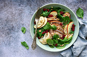 Spinach salad with grilled chicken breast, red apple, dried cranberry and walnuts in a bowl on a light grey slate, stone or concrete background. Top view with copy space.