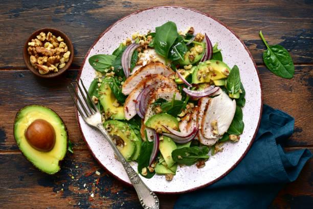 Spinatsalat mit gegrilltem Hühnerfilet, Avocado und Walnüssen – Foto