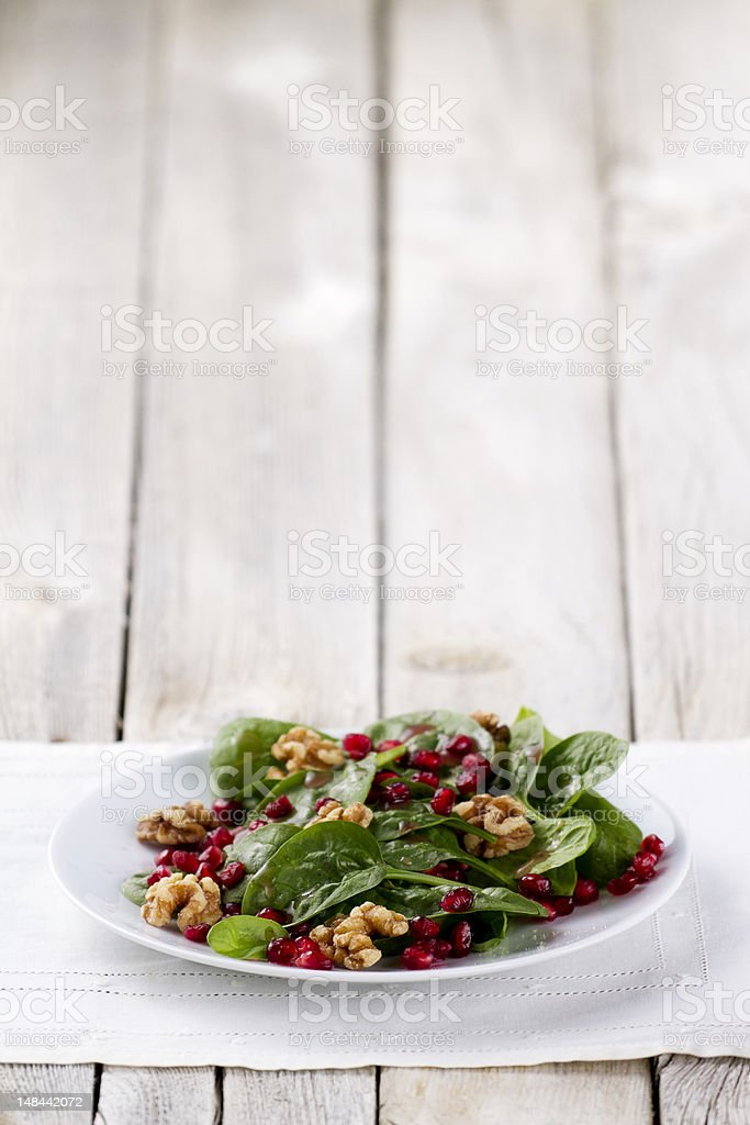 Spinach Salad with Pomegranate Seeds and Walnuts royalty-free stock photo