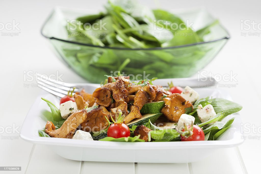 Spinach salad with roasted chanterelle mushrooms royalty-free stock photo