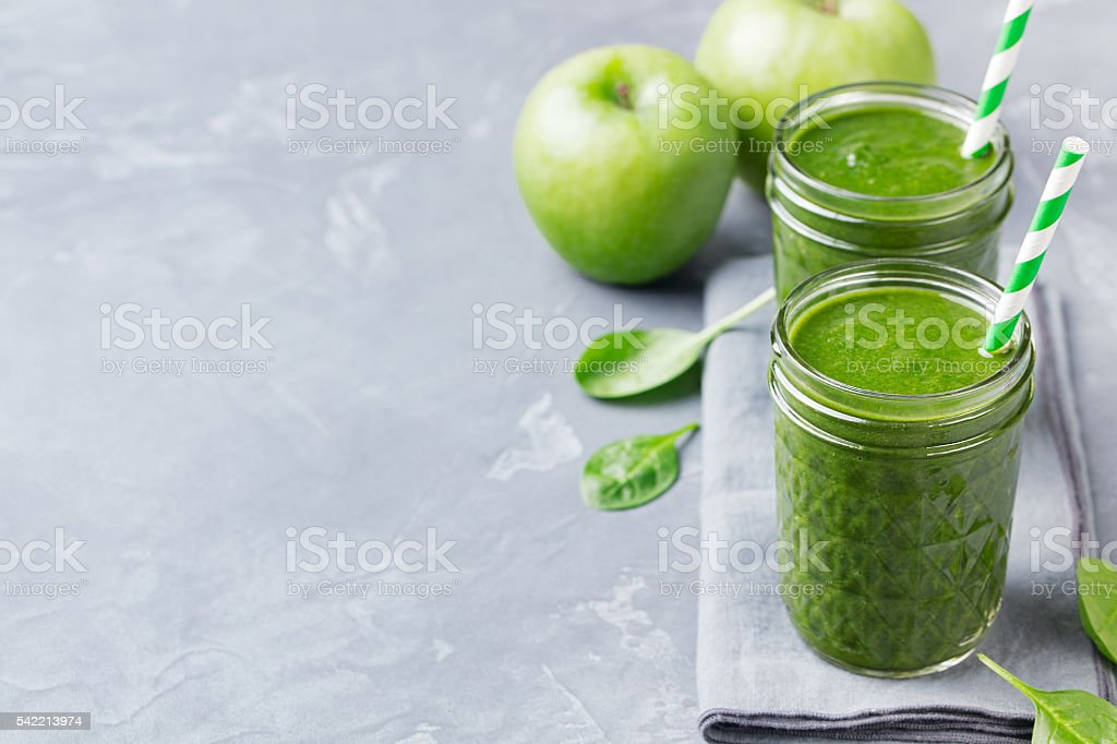 Spinach smoothie Healthy drink in glass jar Grey stone background. stock photo