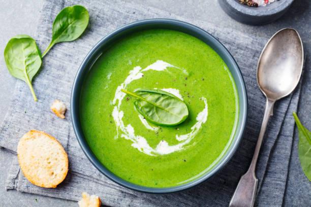 spinat-suppe mit sahne in eine schüssel geben. ansicht von oben. - spinatsuppe stock-fotos und bilder