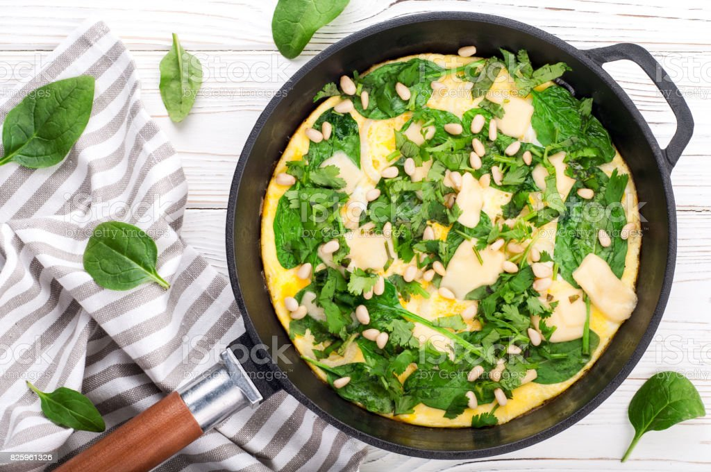 Spinach tortilla in pan on white background. Omelet with eggs, spinach, pine nuts and vegetables. Delicious breakfast or appetizer snack stock photo