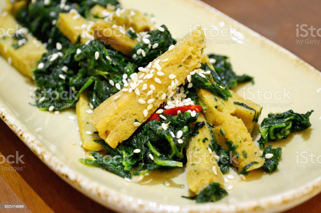 Spinach with seitan in soy sauce with sesame seeds stock photo