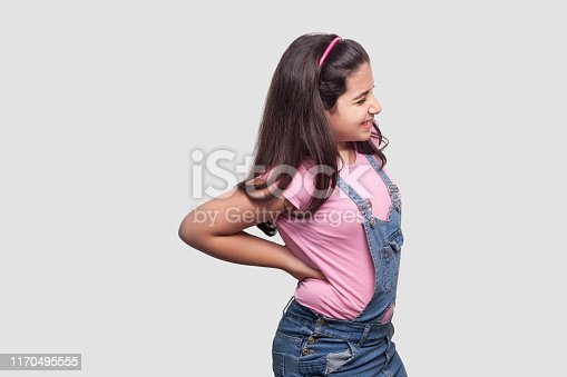 Spine back pain. Profile side view Portrait of sick brunette young girl in pink t-shirt and blue overalls standing and holding her painful back. indoor studio shot, isolated on light gray background.