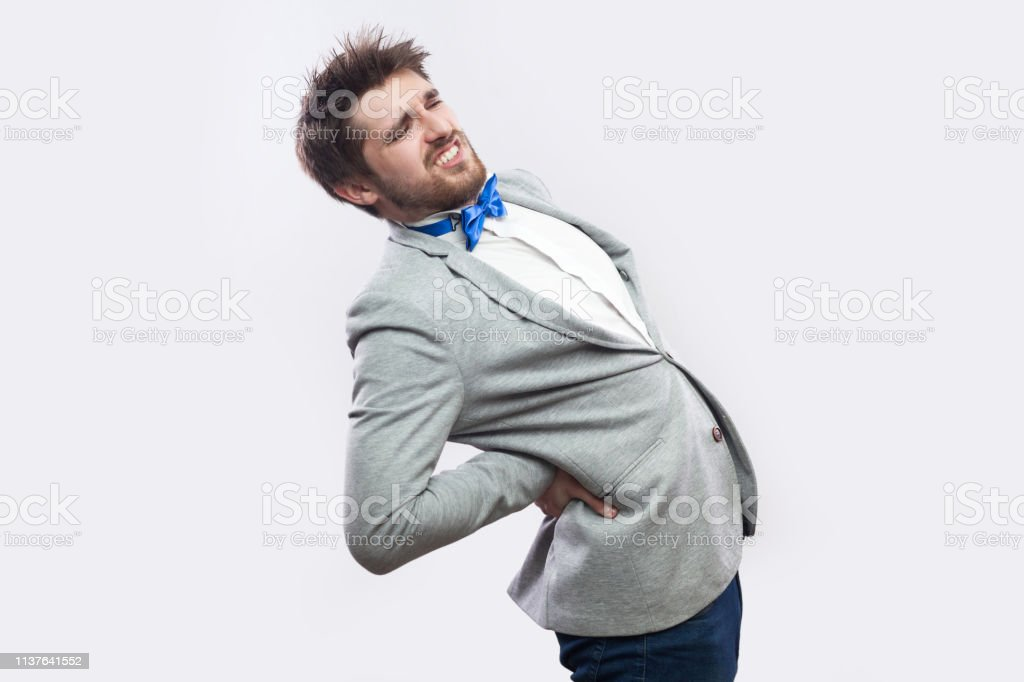 Spine Or Kidney Pain Profile Side View Portrait Of Young Bearded Businessman In Casual Grey Suit And Blue Bow Tie Standing And Holding His Painful Back Stock Photo Download Image Now
