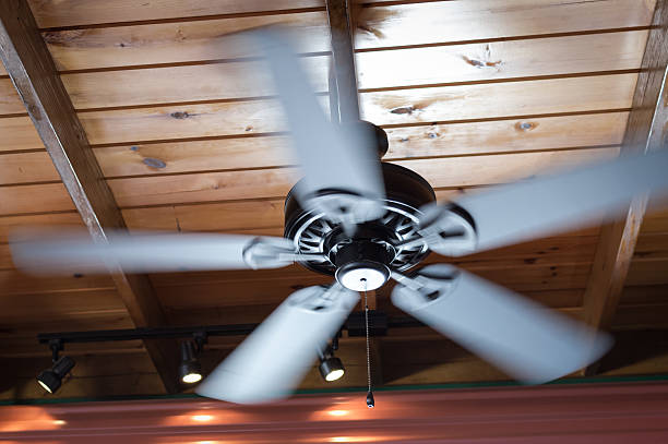 Spinning Ceiling Fan A spinning ceiling fan hangs off of a wooden board ceiling. The fan is turned on and the image exhibits motion blur. The fan is a metallic gray finish. ceiling fan stock pictures, royalty-free photos & images