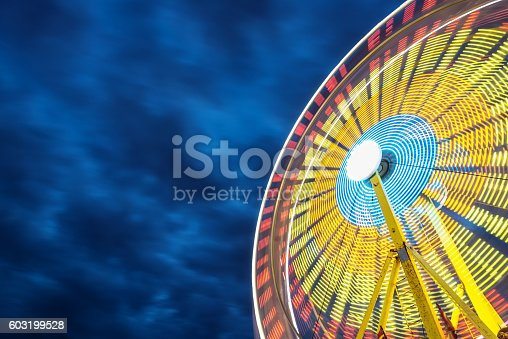 A ferris wheel is full of colour and motion under a canopy of moody clouds.