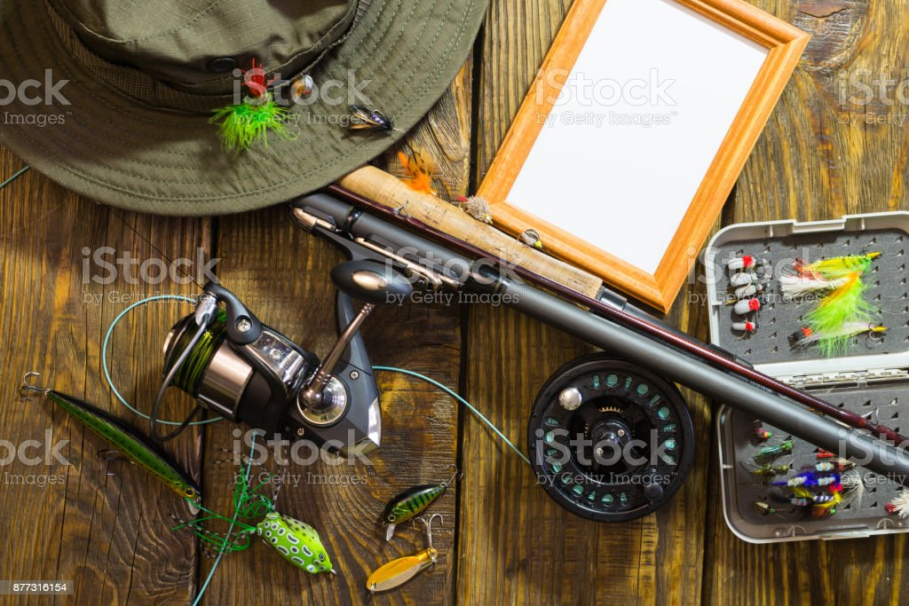 Spinning, fly fishing, flies, spinners, hat and frame for your label lying on a wooden table. stock photo