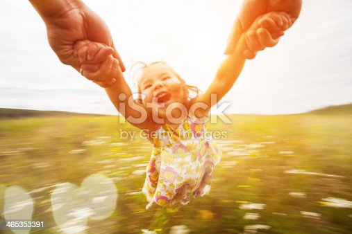 Happy girl spinning around her father in a field. Motion blur.