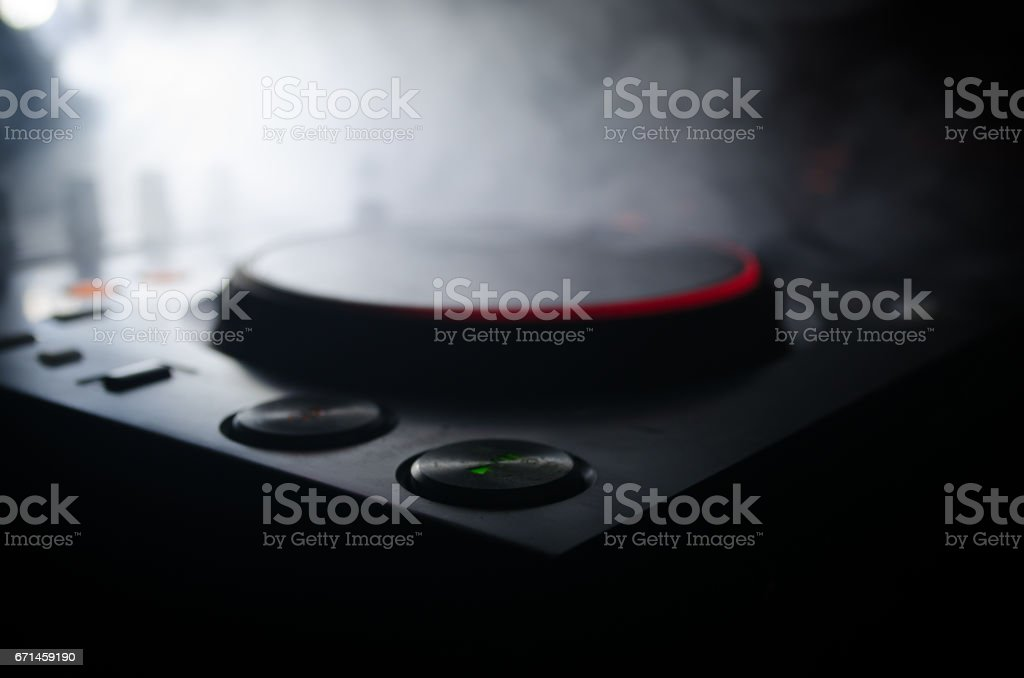 DJ Spinning, Mixing, and Scratching in a Night Club, Hands of dj tweak various track controls on dj's deck, strobe lights and fog, selective focus, close up. Dj Music club life stock photo