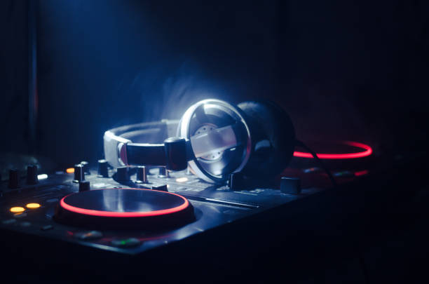 DJ Spinning, Mixing, and Scratching in a Night Club, Hands of dj tweak various track controls on dj's deck, strobe lights and fog, selective focus, close up. Dj Music club life – zdjęcie