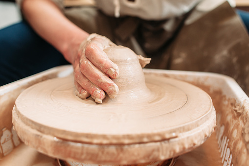 Spinning potters wheel with clay and hand