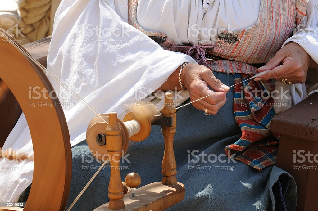 Spinning wheel focus on wool in hand. stock photo