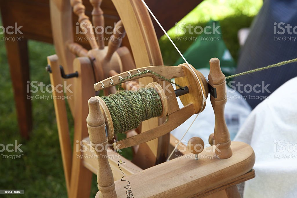Spinning wheel with green wool yarn stock photo