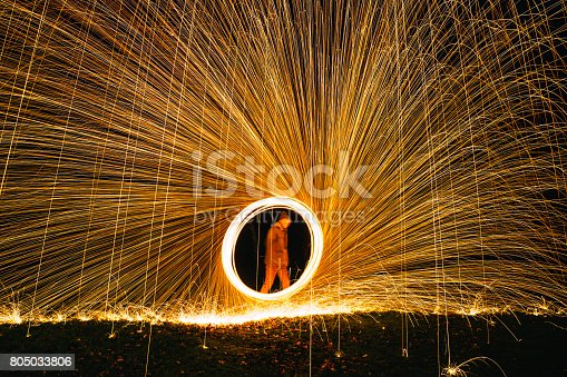 Mature male spinning lit wire wool to create a fan effect.