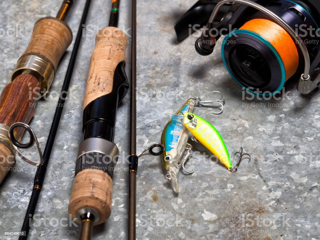 Spinnings, reel and baits on a sheet of tin. royalty-free stock photo