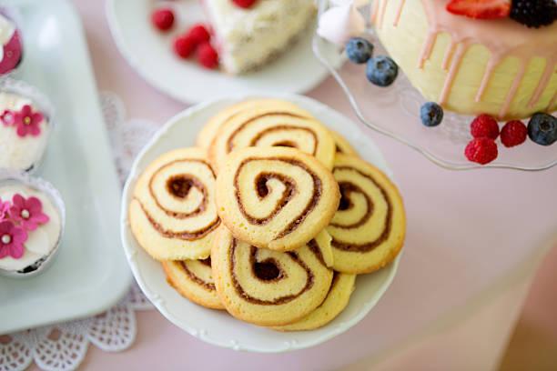 spiral cookies, cake and cupcakes laid on table. - spitzenkekse stock-fotos und bilder