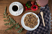 Spiral Cookies with a white cup of coffee and red flower on a wooden table. Handmade biscuits