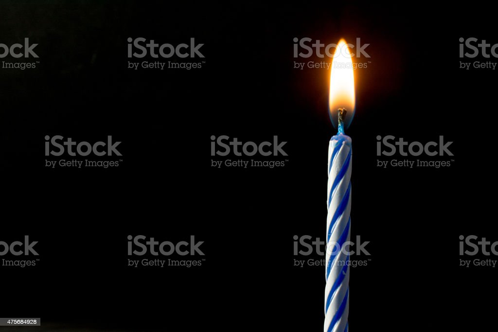 Spiral designed birthday candle with a flame on black. stock photo