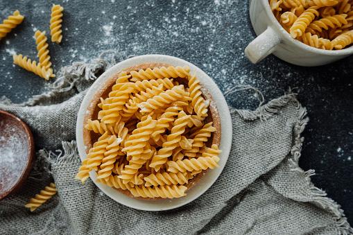 Cuoricini Italian pasta on a fork on spaghetti background. romantic food background.