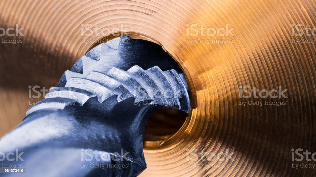 Spiral flute tap and detail of golden metal part stock photo