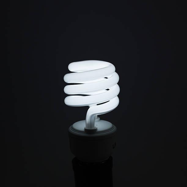 spiral light bulb on dark background - pics of the redtube stockfoto's en -beelden