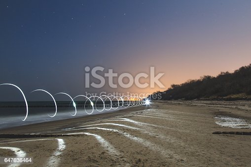 Kuhlungsborn beach in the Baltic sea at night. The light is from a technique light painting with 25 second exposure. Spiral shape should represent abstract tunnel or portal, teleport of some kind