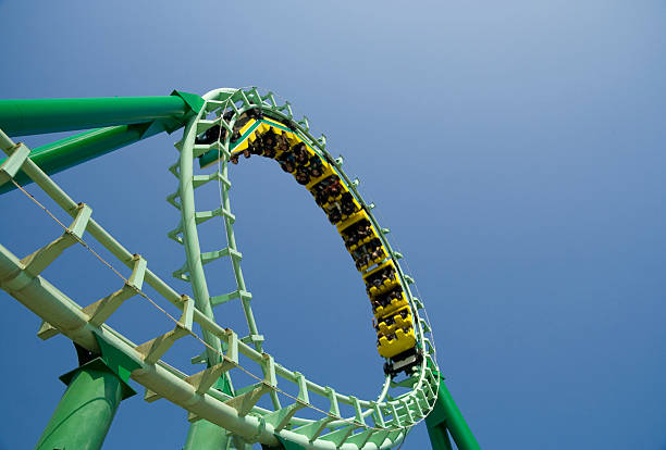 spiral loop of a green steel roller coaster - roller coaster stock pictures, royalty-free photos & images