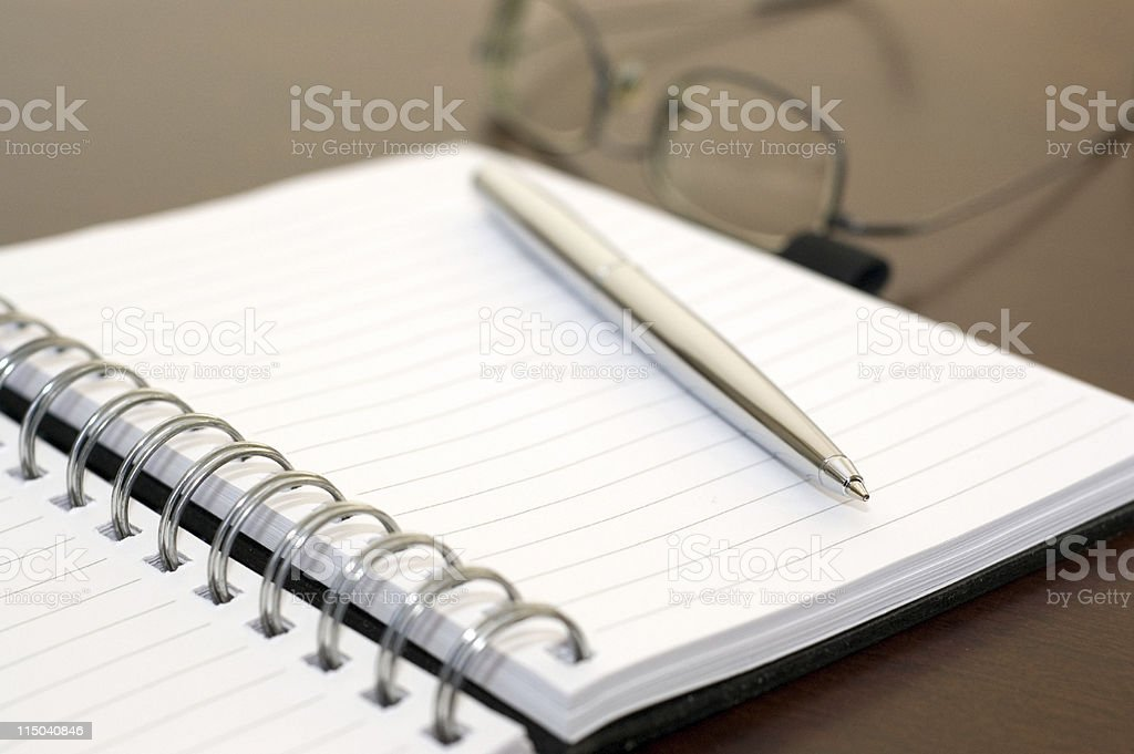 Spiral Notebook Paper Pad, Pen, and Glasses on a Desk royalty-free stock photo
