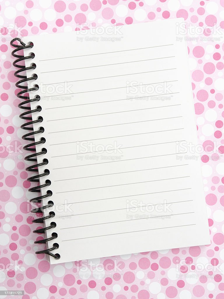 Spiral notepad on pink polkadot surface royalty-free stock photo