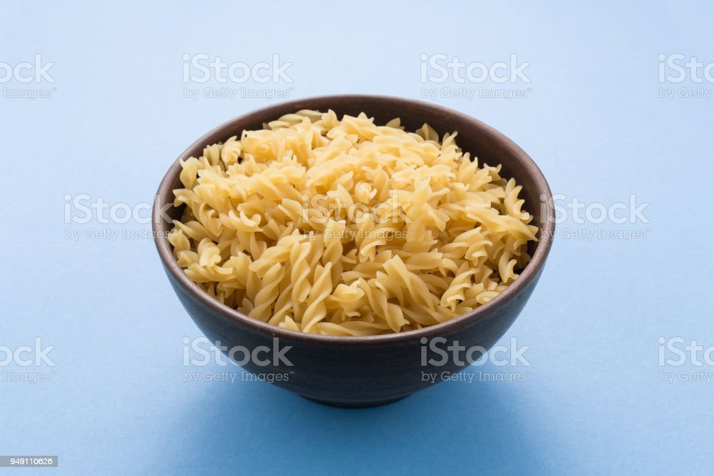 Spiral pasta in bowl on blue background stock photo