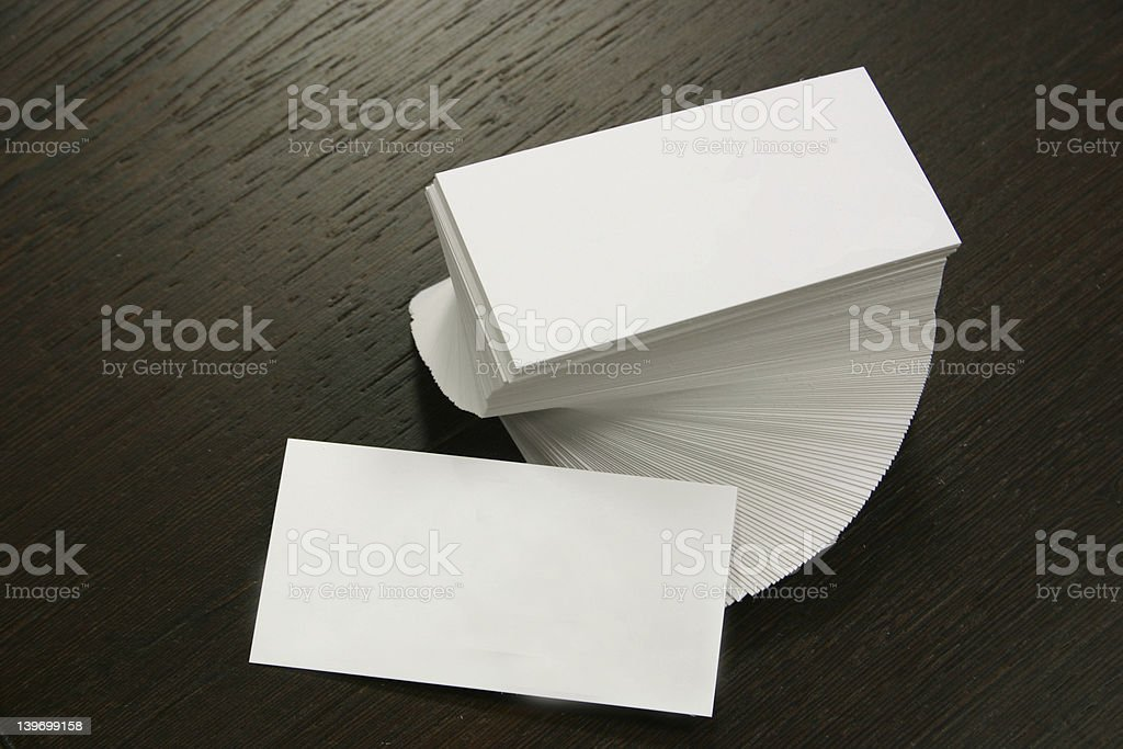 Spiral stack of blank white business cards on dark wood royalty-free stock photo