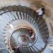 Wide angle view at two business people shaking hands standing at bottom of winding staircase in modern office building, copy space
