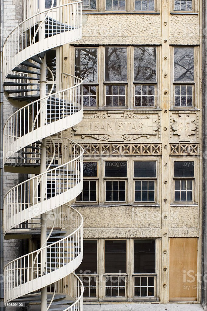 "Spiral stairs on historical Jacqmain Lyceum ""Detail of the historical Lycee Jacqmain with spiral stairs in the Leopold park in Brussels, in the backyard of the European quarter. This beautiful Art Nouveau building dates from 1922."" Architecture Stock Photo"