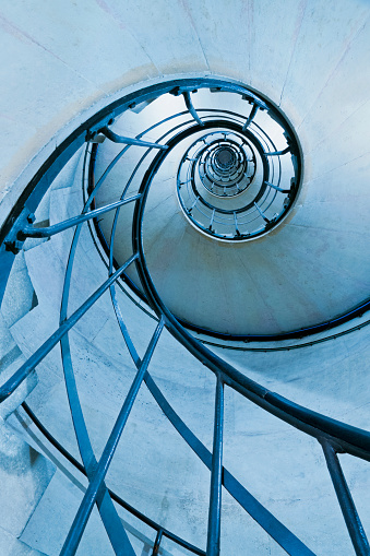 Old-fashioned spiral stairs in Arc de Triomphe in Paris – France  . Blue filter and low angle shot.