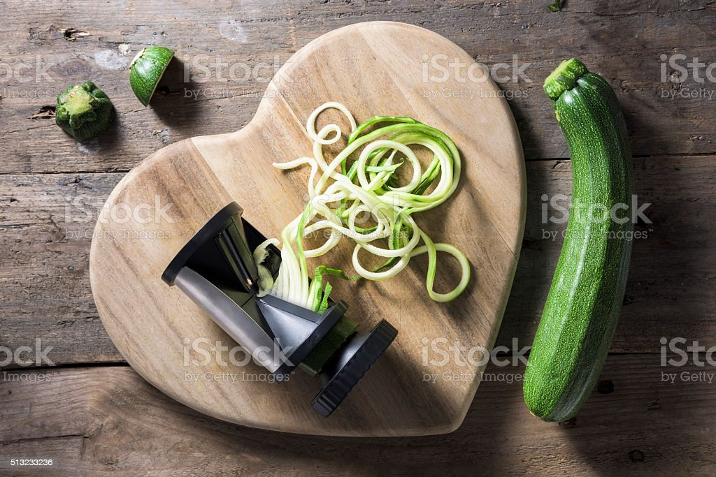 Spiralised courgette beside a spiraliser on heart shaped wooden stock photo