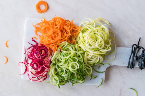 spiraalvormige groenten noodle wortel, rode biet, courgette en komkommer op marble board. - aziatische noedels stockfoto's en -beelden