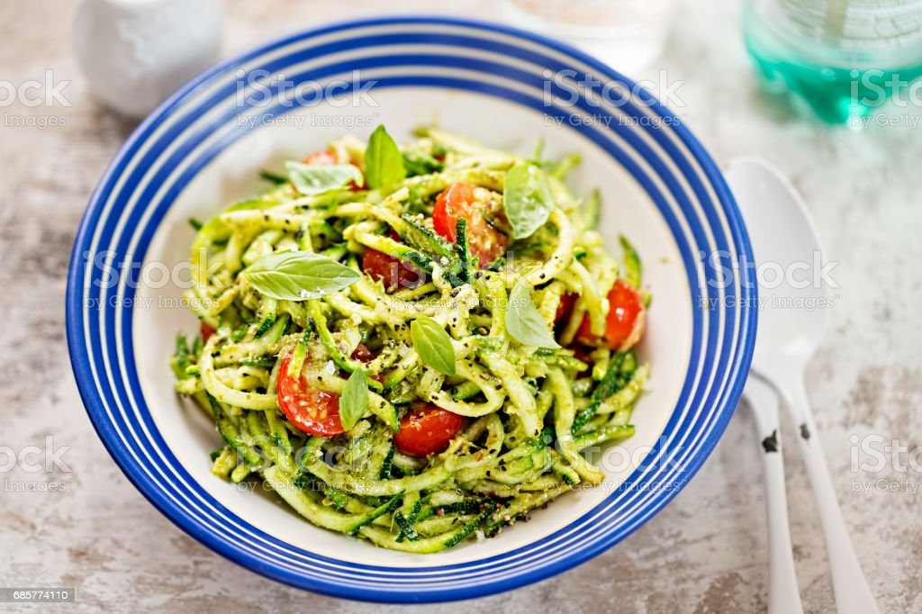 Spiralled courgette spaghetti with green pesto and cherry tomatoes royalty-free stock photo