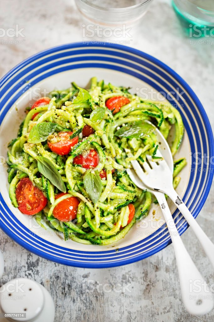 Spiralled courgette spaghetti with green pesto and cherry tomatoes stock photo