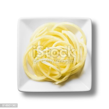 Fresh swede has been spiralised into long thin strands that look like spaghetti noodles. The pale yellow spirals of vegetable are in a white bowl, isolated on a white background with a clipping path. There is a soft shadow underneath the white bowl. They are a healthy non-carb alternative to pasta.