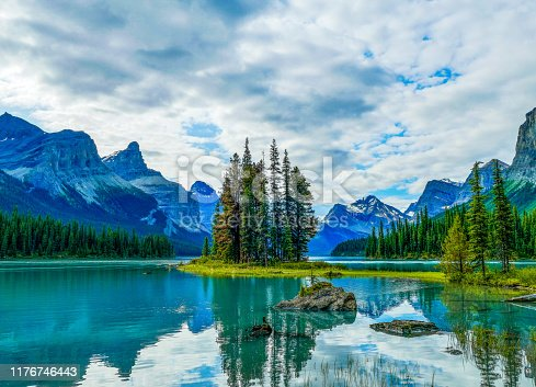 The picturesque Spirit Island is a world famous Canadian Rockies landmark on Maligne Lake, Jasper National Park, Alberta, Canada. In the background is the Hall of the Gods, with the prominent peaks of Mount Paul as well as Monkhead Mountain to the left of Spirit Island.