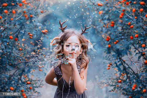 spirit of the forest in the form of a child in a light brown dress, a baby deer playfully leads into the forest, the little faun keeps the secret and hides in the berry bushes, the winter cold colors.