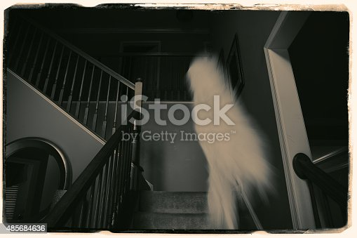An old antique photograph of a staircase with a spirit caught on film.